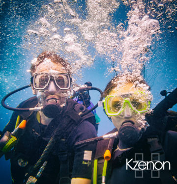 Man and woman scuba divers in tropical sea diving up
