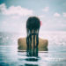 Woman tourist in infinity pool of hotel resort at ocean