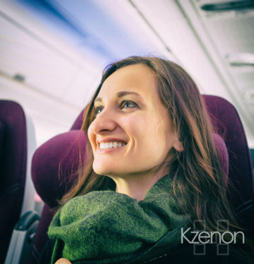 Happy woman tourist with green scarf during flight in plane to her vacation