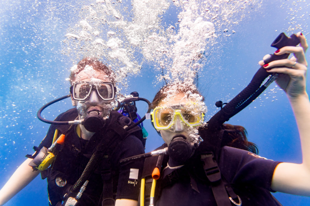 Man and woman scuba divers in tropical sea diving up after underwater excursion