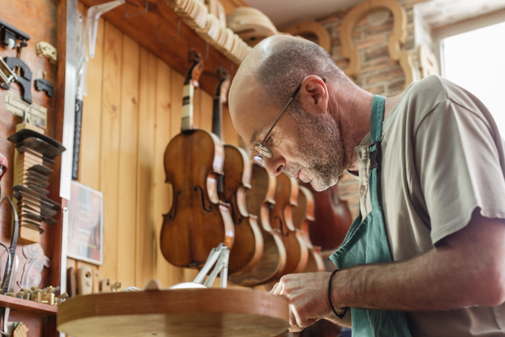 Violin maker being absorbed by work on a new instrument