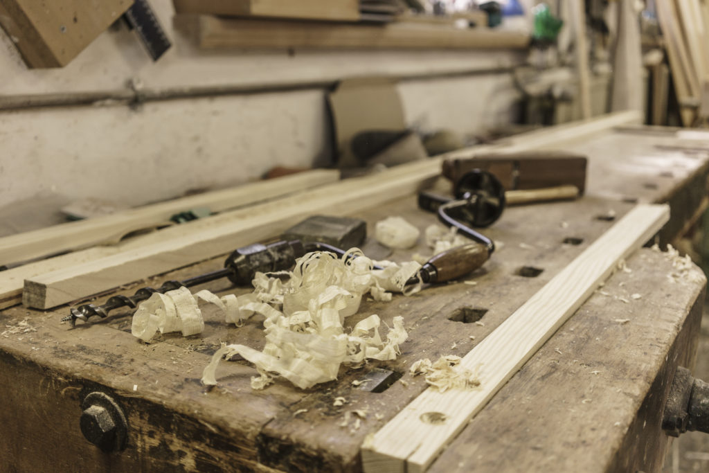 Mechanic drill, plane and wood shavings lying on workbench at carpentry workshop