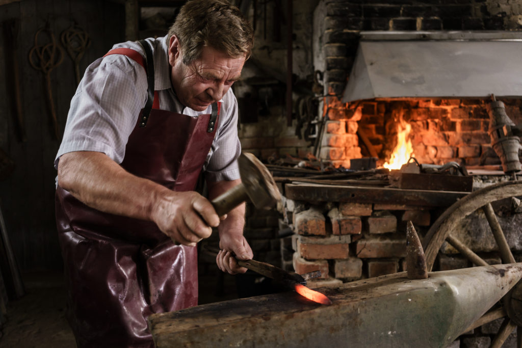 Blacksmith hammering on red hot pick laying on the anvil in his workshop